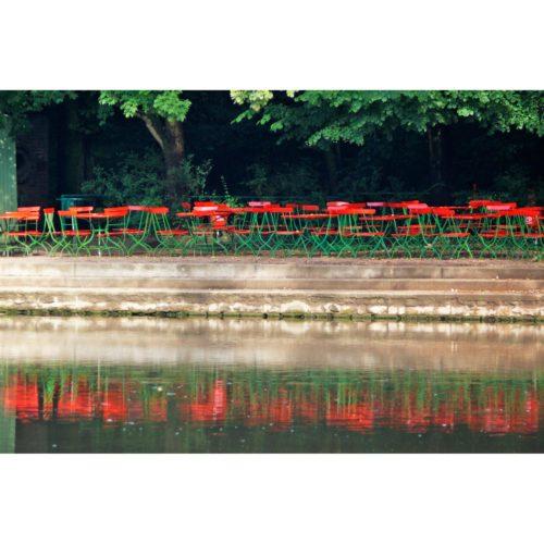 Rote Stühle am Wasser